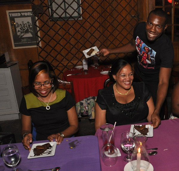 Jermaine Barnaby/Photographer Hope Mc Millan- Cowan (right) and Simone Mahabeer as they are served dessert at The Gleaner's Pre-Restaurant Week Dinner Promotions 2013 with Karin Cooper and guests at  Red Bones on   Tuesday, November 5, 2013.