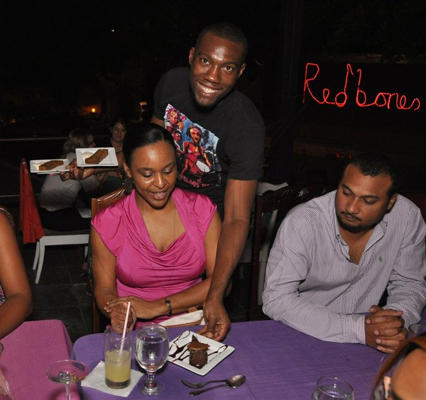 Jermaine Barnaby/Photographer Kalia- Gaye Dunbar (left) and husband Richard Dunbar being attended to by waiter Leonard Wilson during The Gleaner's Pre-Restaurant Week Dinner Promotions 2013 with Karin Cooper and guests at  Red Bones on Tuesday, November 5, 2013.