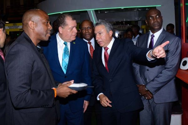 Shorn Hector/Photographer  Brain Bennette-Easy General Manger Digicel Jamaica (left) ishowcasing the lates in technolofy that digicel has to over to The Hon. Audley Shaw and Metry Seaga at Expo Jamaica 2018 Opening Ceremony at the National Indoor Sports Complex on April 19 2018