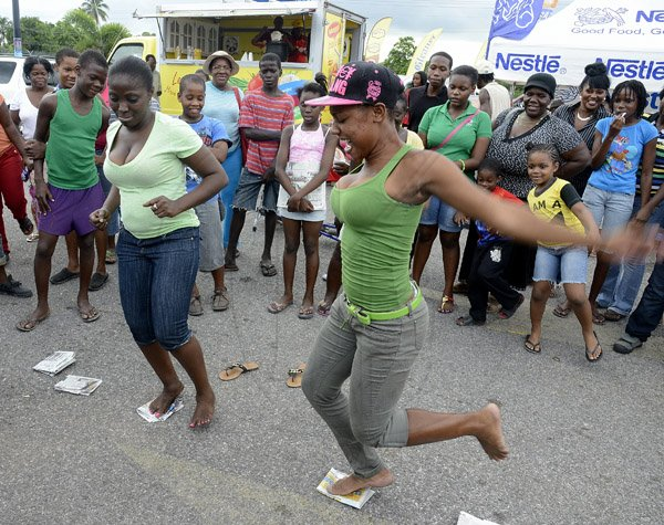 Gladstone Taylor / Photographer  Sasha-Gaye Savage (right) loses her balance in the news paper dance contest leaving Tashna Benett the victor as seen at the Gleaner company food moth promotion held at shoppers fair super market on brunswick avenue, spanish town on saturday