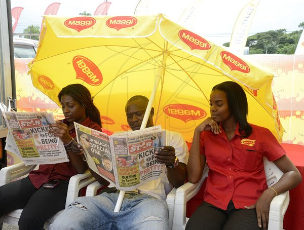 Gladstone Taylor / Photographer  These three Maggie representatives take a minute to check out the saturday star as seen at the Gleaner company food moth promotion held at shoppers fair super market on brunswick avenue, spanish town on saturday