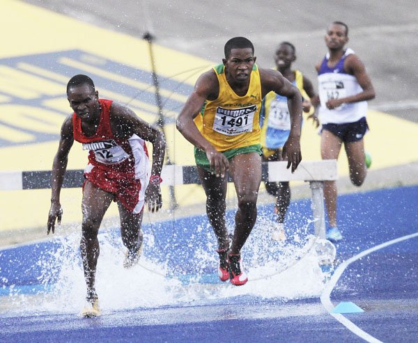 Ricardo Makyn/Staff Photographer Left Nembhard Palmer  of Bellefield tries to catch up to Roshawn Johnson of St Jago High School  leading the field to win heat 2 of the Boys' Open 2000 Steeple Chase at the National Stadium at Boys and Girls Champs 2012