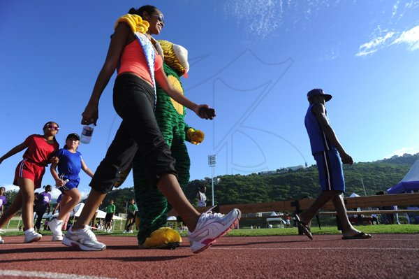 Ricardo Makyn/Staff Photographer Miss Jamaica World Deanne Williams with the Reggae Tiger  at the Heart Fund run titled Run for your Heart at the Stadium  East Track on Sunday 25.11.2012